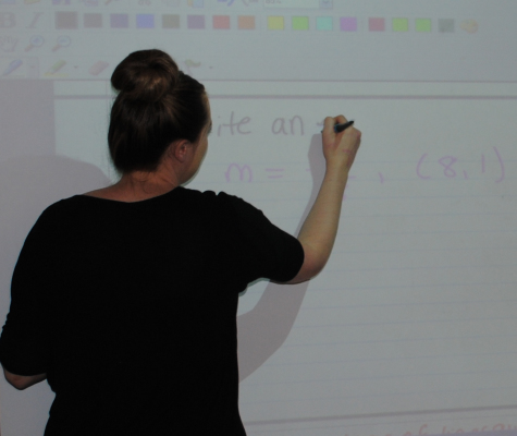 While reviewing the homework, Ms. Corrigan instructs her students on how to complete the problem.