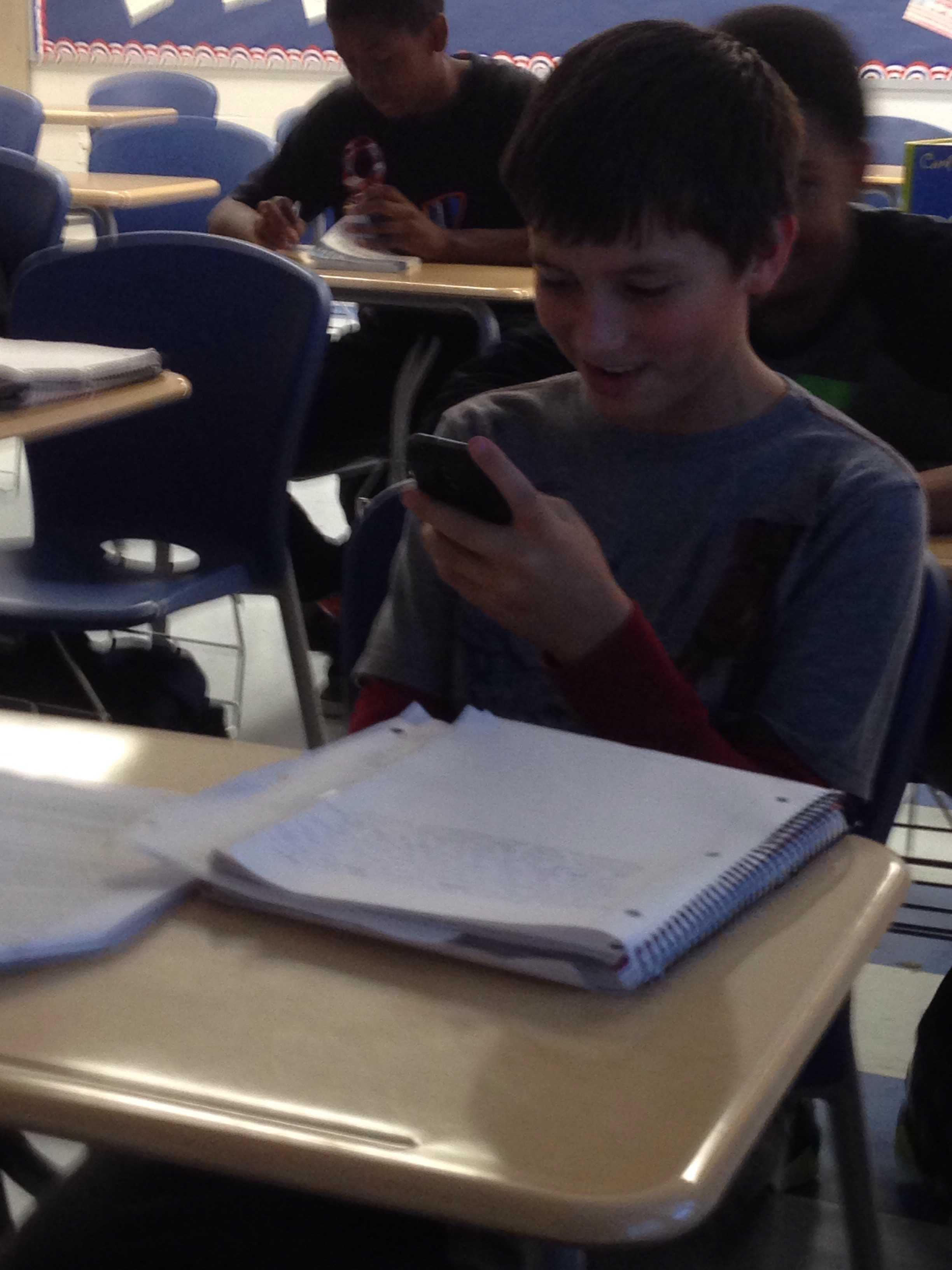 Researching articles on genocide for an essay in English class, Freshman Sean Dressler uses his phone with the teacher's permission.