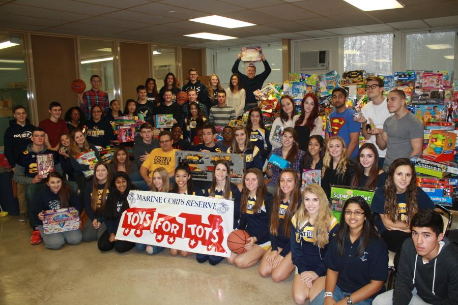 Students take a picture with all the toys that were collected.