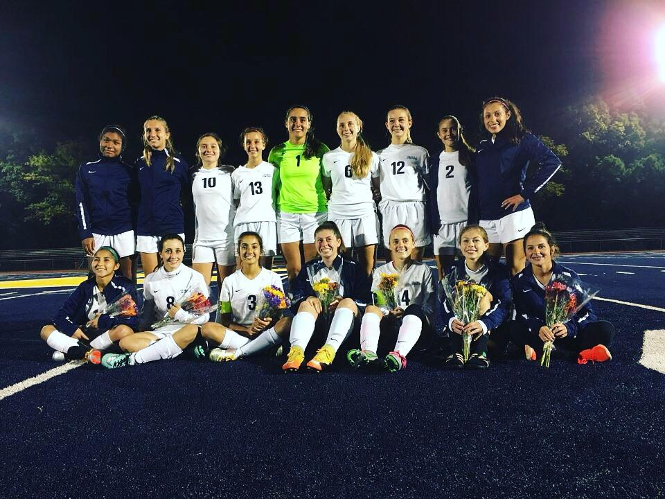 The varsity girls soccer team pose for a picture after successfully getting a W on their Senior Night.
