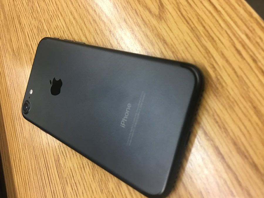 Displaying the all new matte black color, the iPhone 7 rests upon a wooden desk.