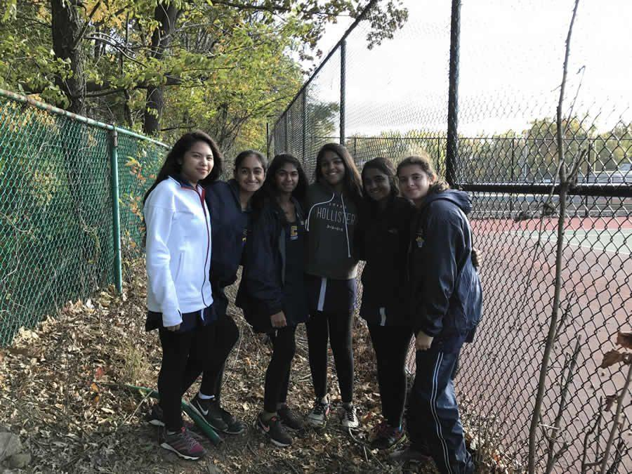 Happily posing behind Colonia High School's tennis courts, members of the Girls Tennis team await the end of the matches.