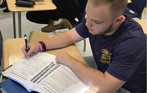 CHS Tomorrow's Teachers student, Brian Demcher, working in their textbook.