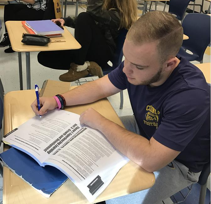 CHS Tomorrow's Teachers student, Brian Demcher, working in their textbook.