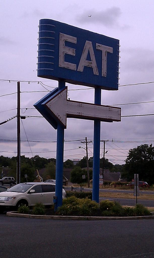 The big neon sign placed in front of the restaurant to help attract customers.