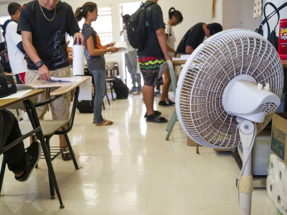 Fans are used to cool an overheated classroom in this American school. (AP Photo) ORG XMIT: POS2016090916573916