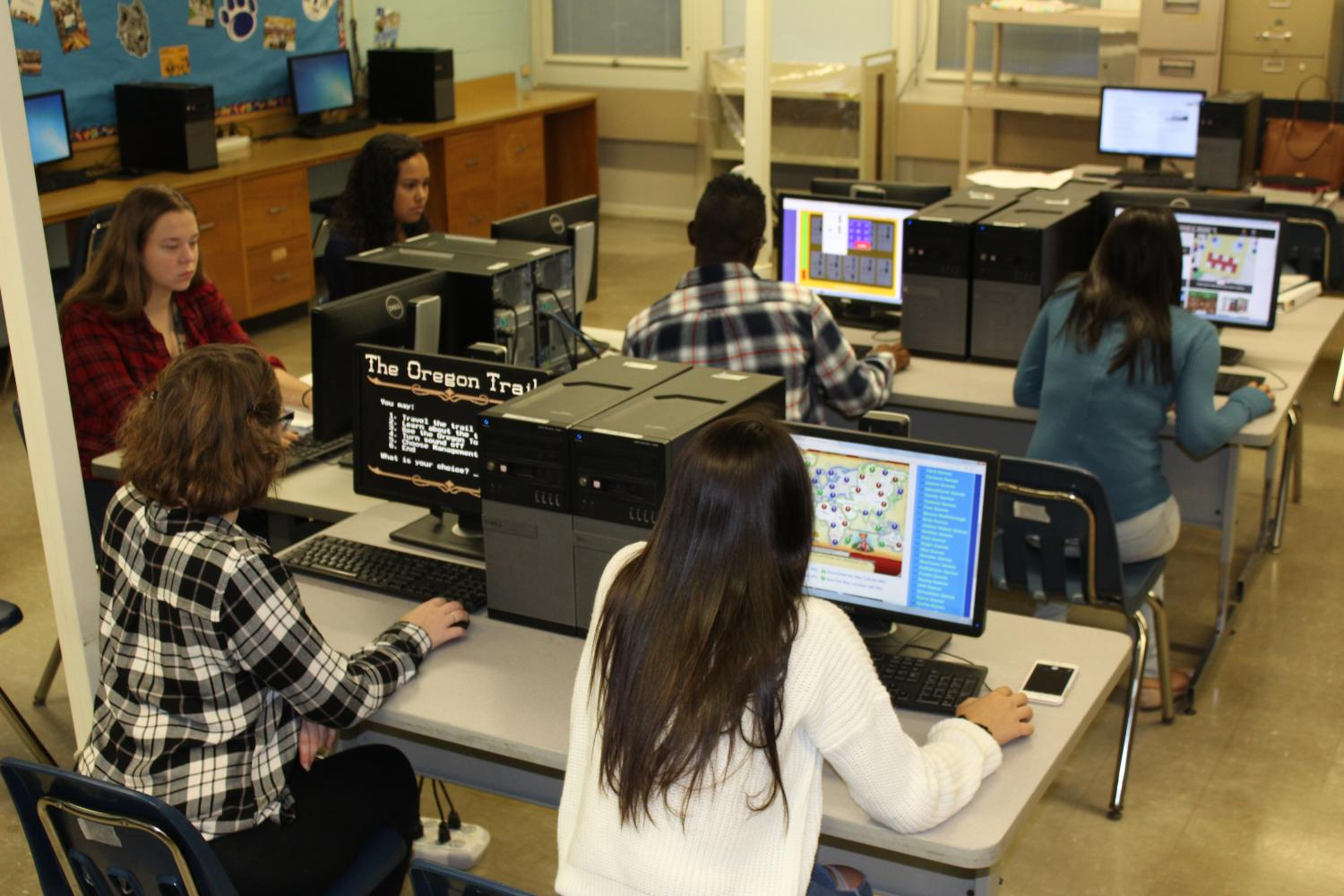 Captivated by interactive educational games, students huddle over their computer excited to learn.