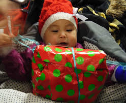an image of a baby receiving a gift on Christmas.