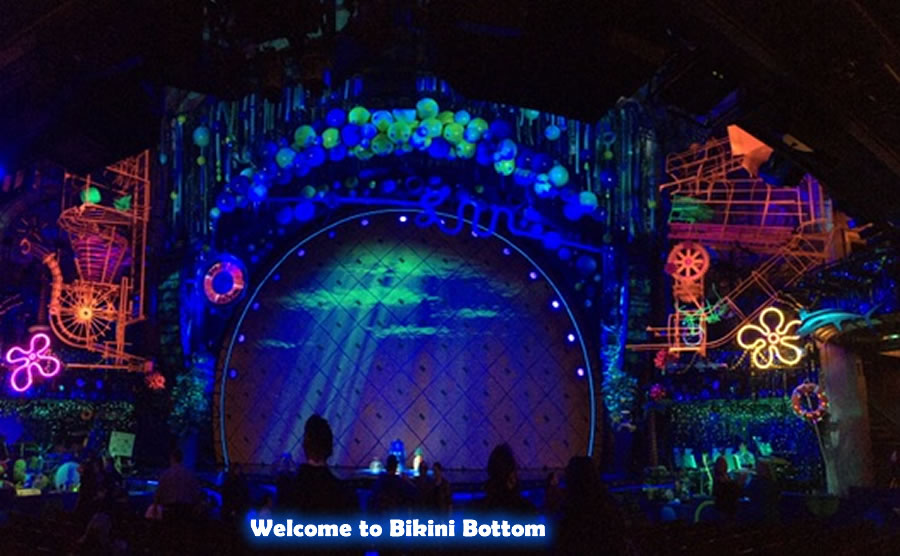 The colorful stage displayed under black lights for Spongebob The Musical.