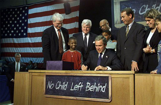 US PresidentGeorge W. Bushsigns into law the No Child Left Behind Act, surrounded by children and supporters.