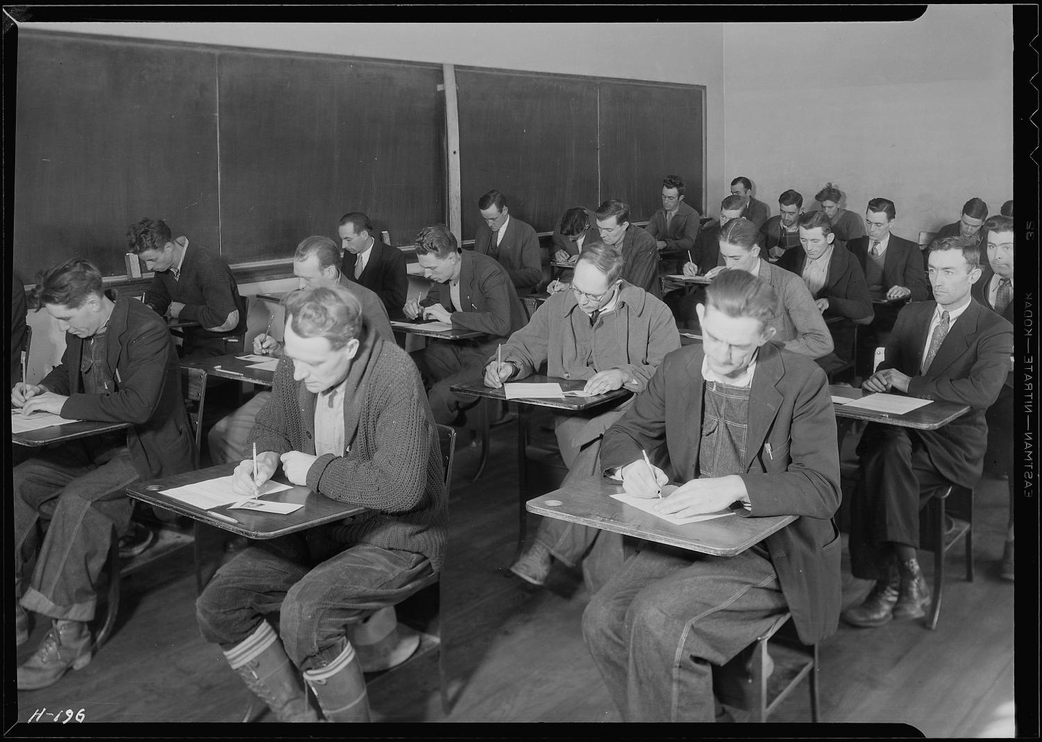 A bunch of unskilled men taking an exam in a high school
