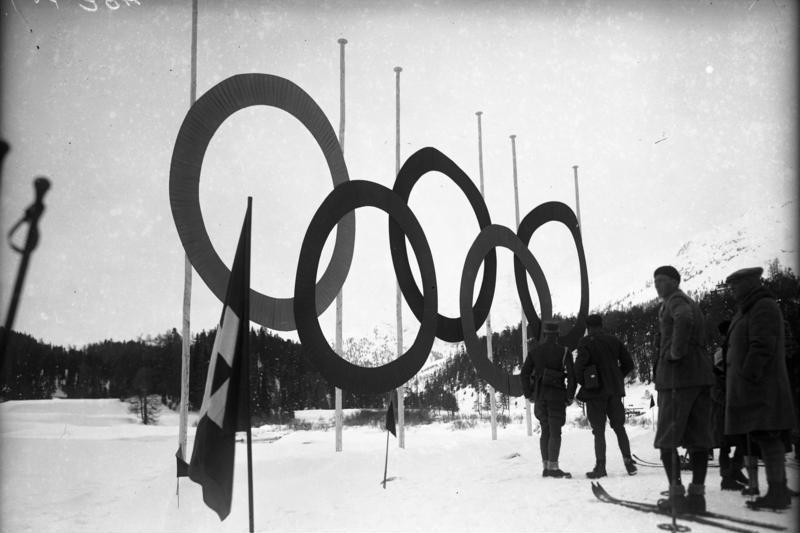 The Olympic Rings Stand tall, surrounded by athletes during the first winter Olympics.