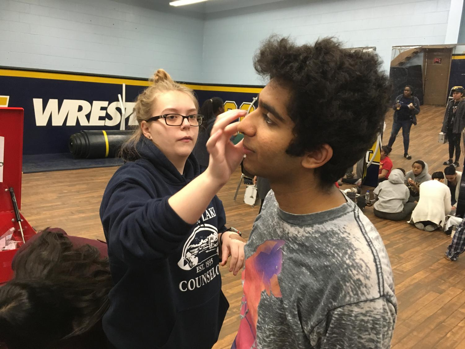 Makeup Supervisor Haley Vaughn applying makeup to Senior Ashank Punj to accentuate his features.
