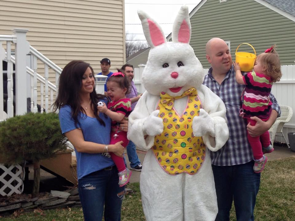 Meeting the Easter Bunny, Bryn Ellmyer clings to her mother, Melissa Ellymer in fear while twin sister Alissa hides her face from the bunny while father, Steven Ellmyer holds her.