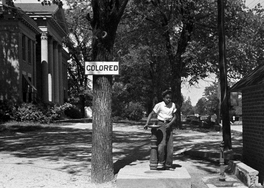 A young child drinks at a segregated fountain in the late 1930s: a time period filled with language still used today.