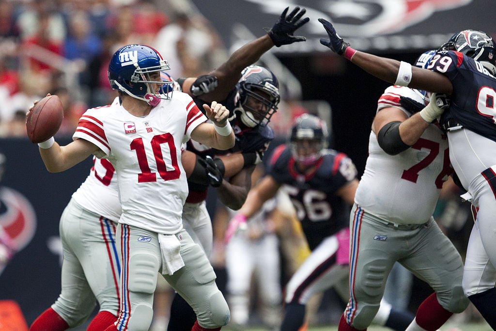Seen here is New York Giants quarterback Eli Manning, number 10 (left), being surrounded by approaching Texans players looking to sack him.