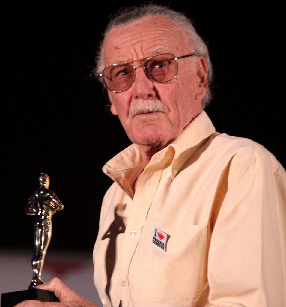 Holding an Oscar Stan Lee looks out into the audience.