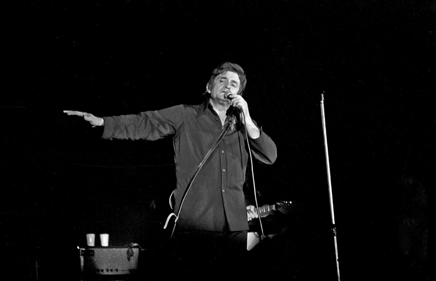 Performing Ring of Fire, Johnny Cash sings at the concert years after its debut.