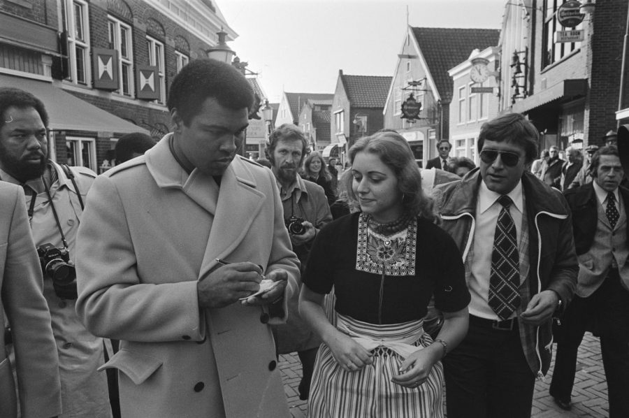 Seen here is a picture of boxing legend, Muhammad Ali, signing autographs for some of his fans.