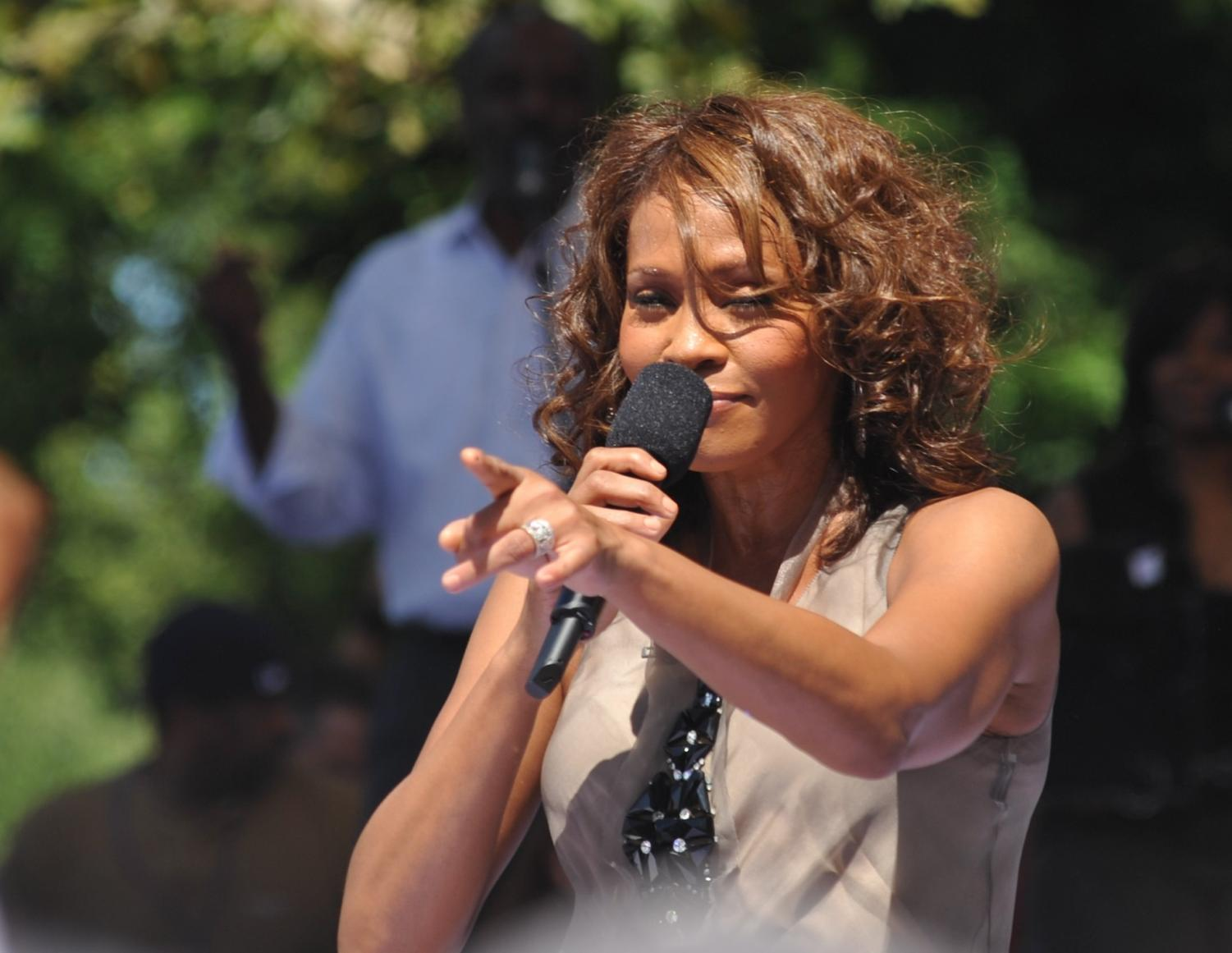 Singing at an outdoor concert, Whitney Houston performs I will always love you.
