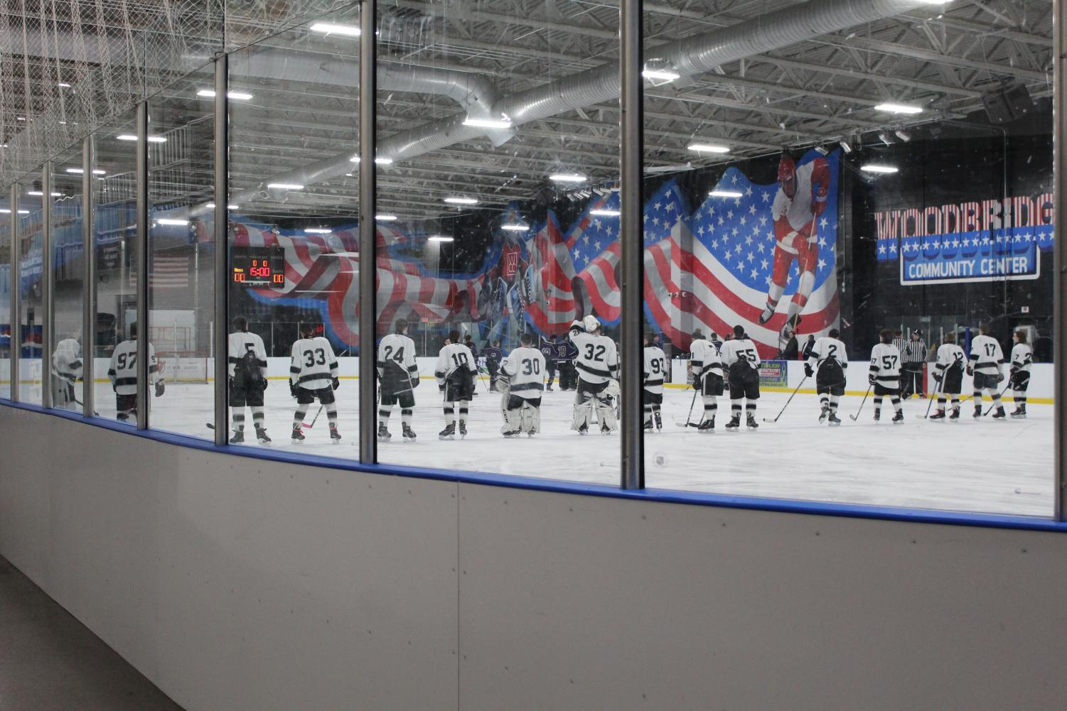 The hockey team lines up before their game starts, to listen to the National Anthem.