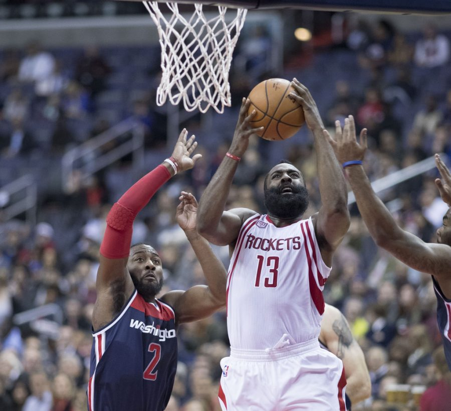 Seen here is reigning MVP James Harden (#13, right), going up for a layup between two Wizards defenders.