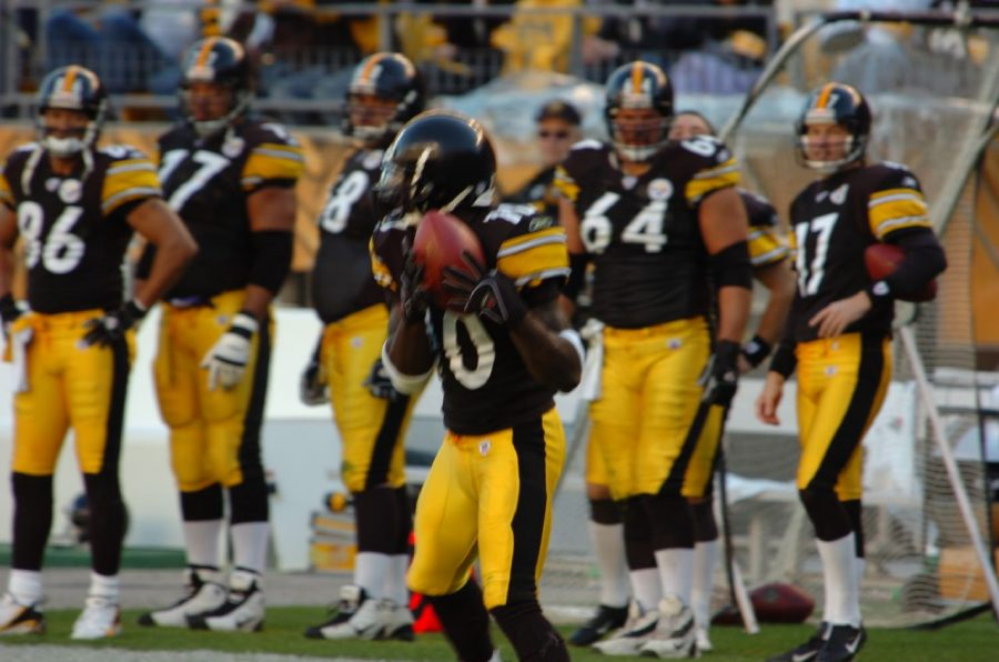 Seen here is Steelers receiver and Super Bowl XLIII MVP, Santonio Holmes (#10, middle) catching a pass near the sidelines.