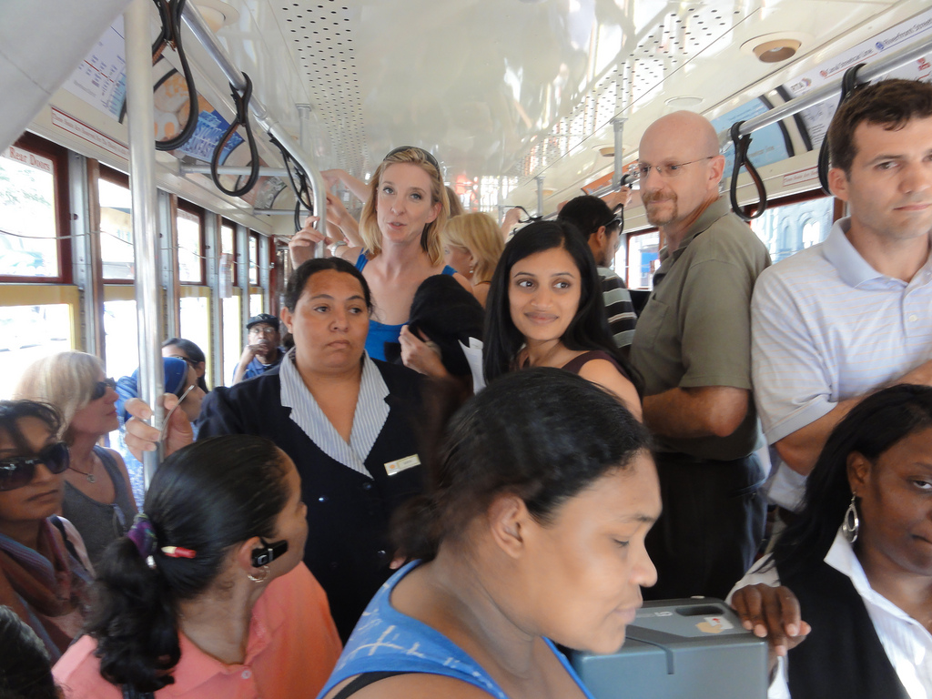 The small bus was chockablock or crammed with people.