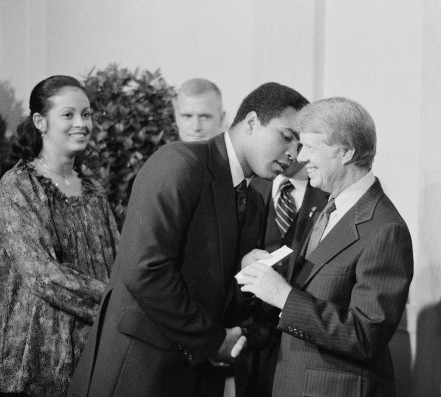 Seen here is boxing legend Muhammad Ali (leaning over), formerly known as Cassius Clay, talking to President Jimmy Carter (right).