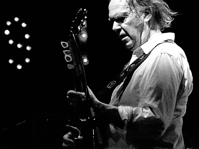Jamming out with his guitar, Neil Young, plays from his album Harvest.