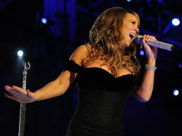 Passionately singing one of her singles, Mariah Carey, performs at the concert.