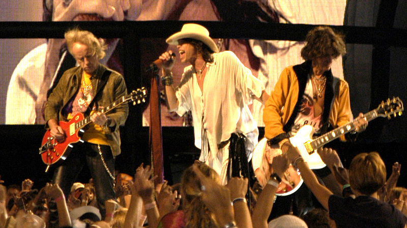 Singing Walk this Way, Aerosmith performs for their fans.