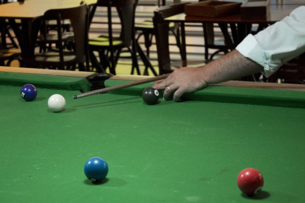 Seen here is an example of a billiards table with someone playing on it.