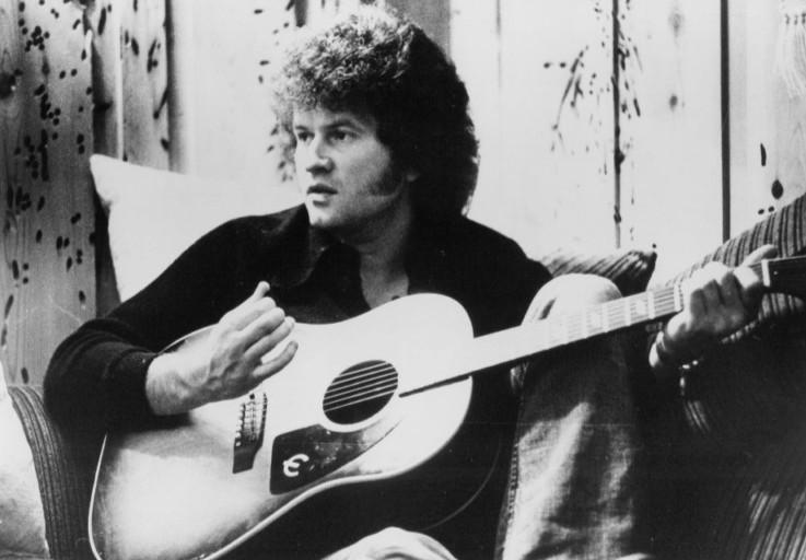 Playing guitar, Terry Jacks write his single Seasons in the Sun.