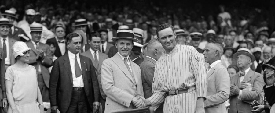 Seen here is an image of two men shaking hands at a baseball game in the 1960s.