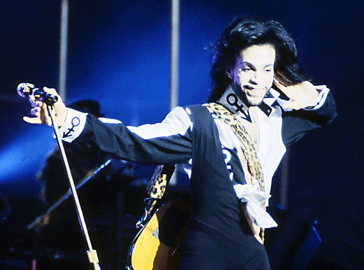 Encouraging his fans to sing along with him, Prince performs at the concert.