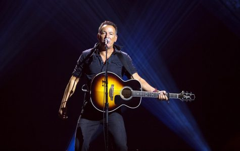 Performing a song from his album Born in the USA, Bruce Springsteen jams out with his audience.