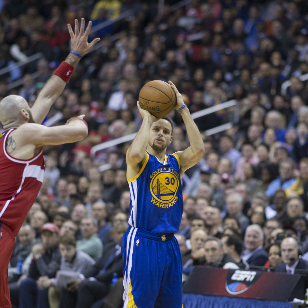 Seen here is NBA star Stephen Curry, shooting a three pointer over a Wizards' defender.