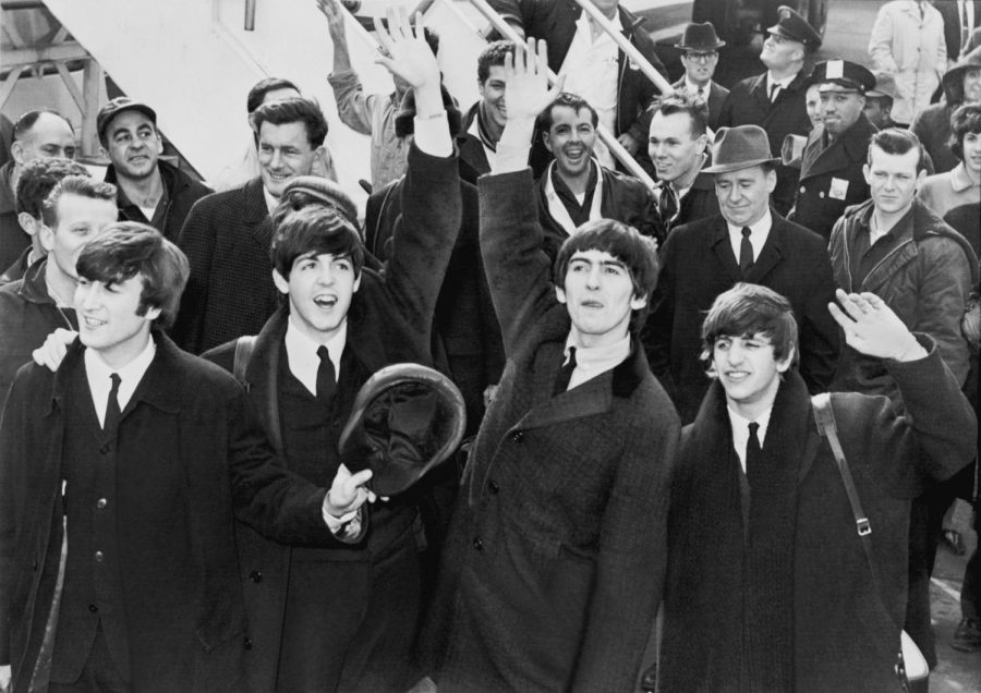 Waving to their loyal fans, The Beatles arrive in America.