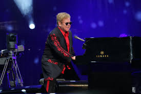 Performing Rocket Man, Elton John, sings at the concert.
