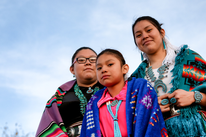 Three+beautiful%2C+proud+and+traditional+Native+American+Navajo+sisters+in+traditional+clothing+posing+outside+in+Monument+Valley+Arizona