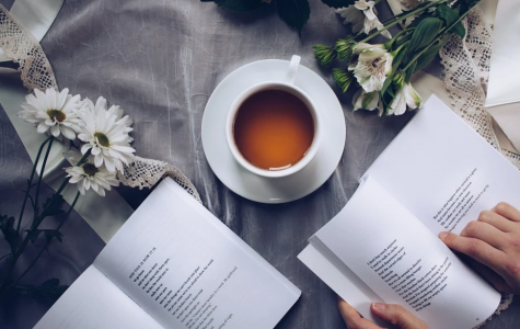 An image of a person with a poetry book and a cup of tea in front of them