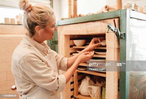 Shot of a artisan placing earthenware in her kiln