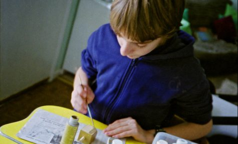 At home, the boy begins to paint a wooden dreidel the color yellow.