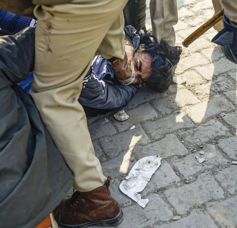 A+Police+Officer+pinned+down+a+protester+named+Ranjit+Singh+with+his+foot.+