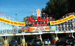 A group of people in the popular amusement park begin to enter via car as they pay for parking.