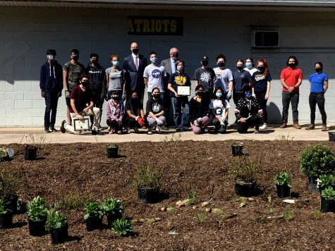 While finishing planting in the field  house rain garden, Mayor McCormac awarded Frankie Vasquez and Colonia High School with renewable energy awards.