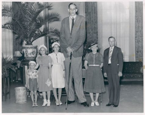 Pictured above is Robert Wadlow, the tallest man ever recorded. Hes pictured with women, children, and a man of standard sizes to show contrast.